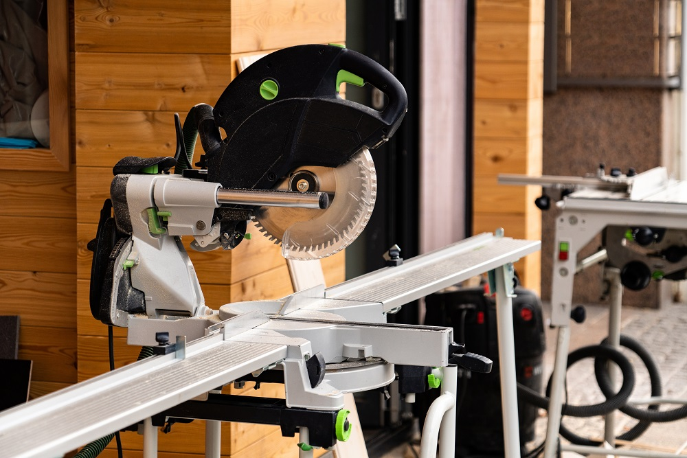 Sliding compound mitre saw. Electric tool for construction of wooden house.